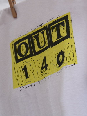 A close-up photo of a t-shirt with the OUT140 logo hanging from a washing line.