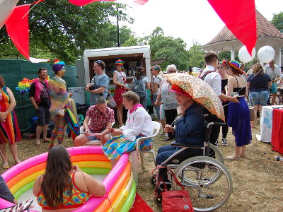 The Safe Art Space at Chapelfield Gardens, with many colourful people and a rainbow paddling pool.